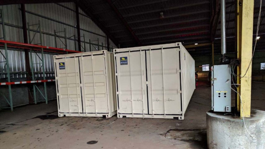 double storage container shipping container with cargo doors conexwest sign inside factory facility