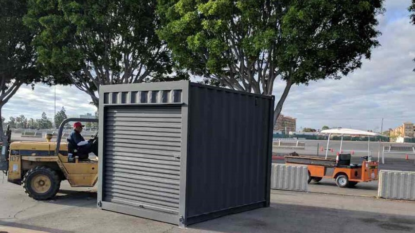trees container shipping container black storage container with roll up door on field