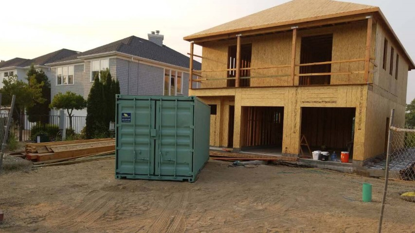 contracted use shipping container storage container on site rebuilding house house frame green color storage container grey sky