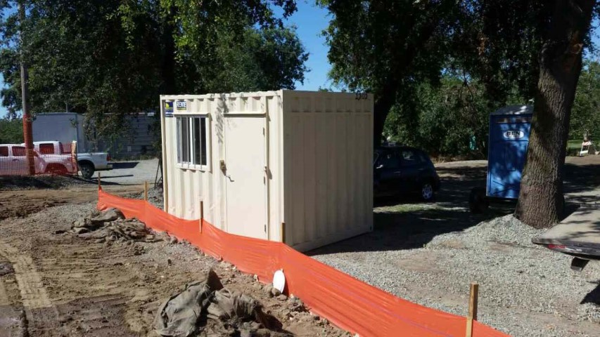 contracted use shipping container storage container office container window man door orange tape mud dirt trees