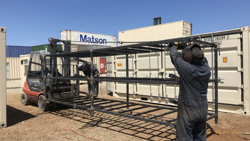 workers constructing container frame blue sky black outfit black metal bars cream color shipping container storage containers