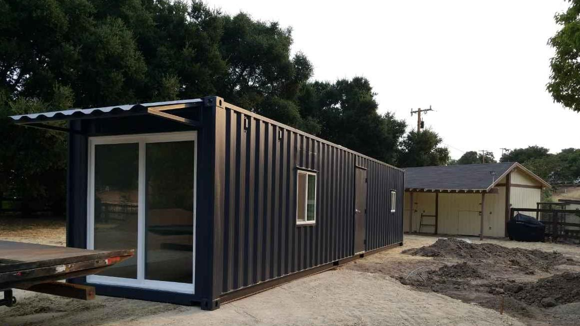 black storage container container home modified container grey sky black color