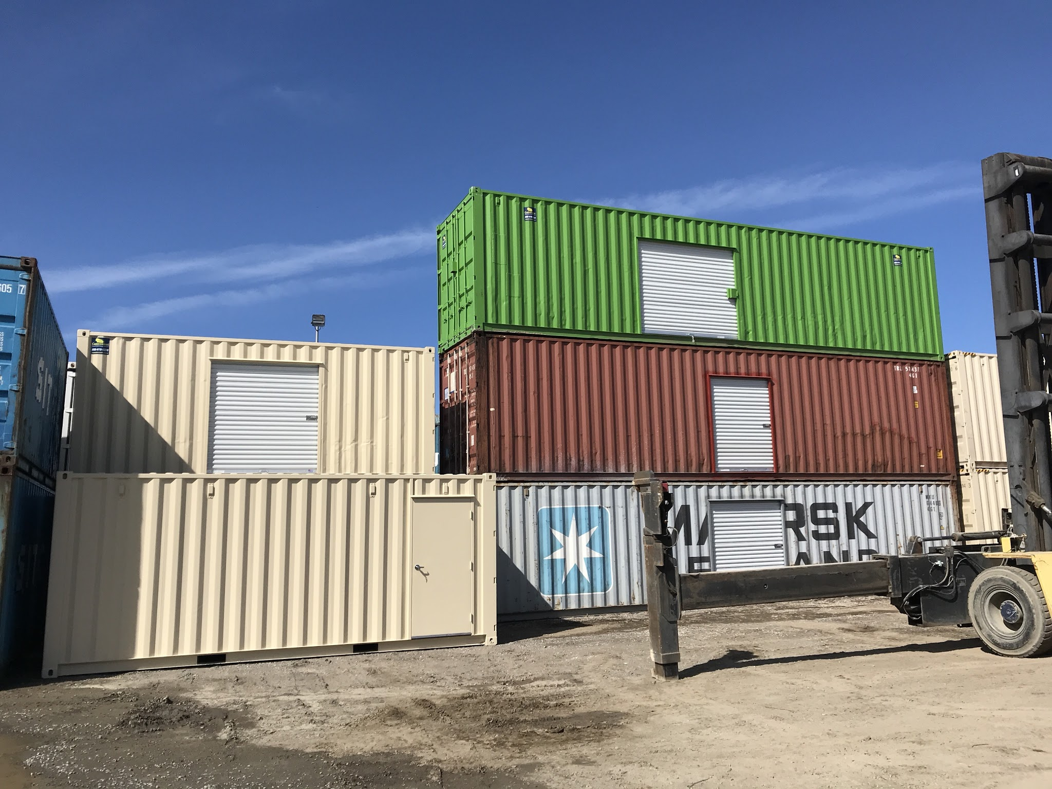 Roll up doors of shipping containers stacked on top of each other