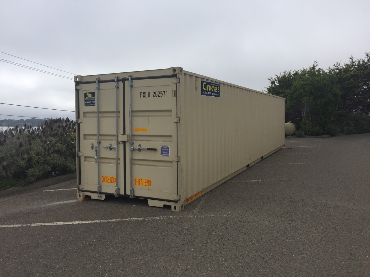 Shipping container on the side of the road with cargo doors