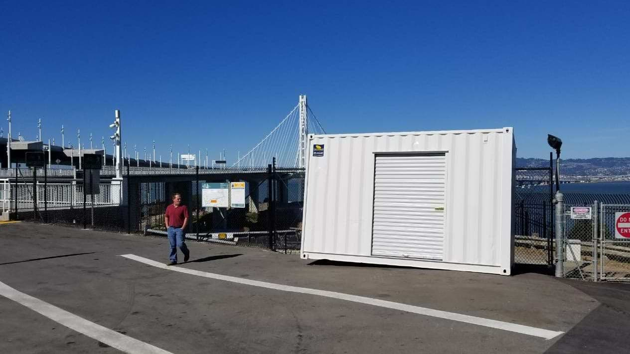 shipping container roll up door blue sky bay bridge San Francisco California