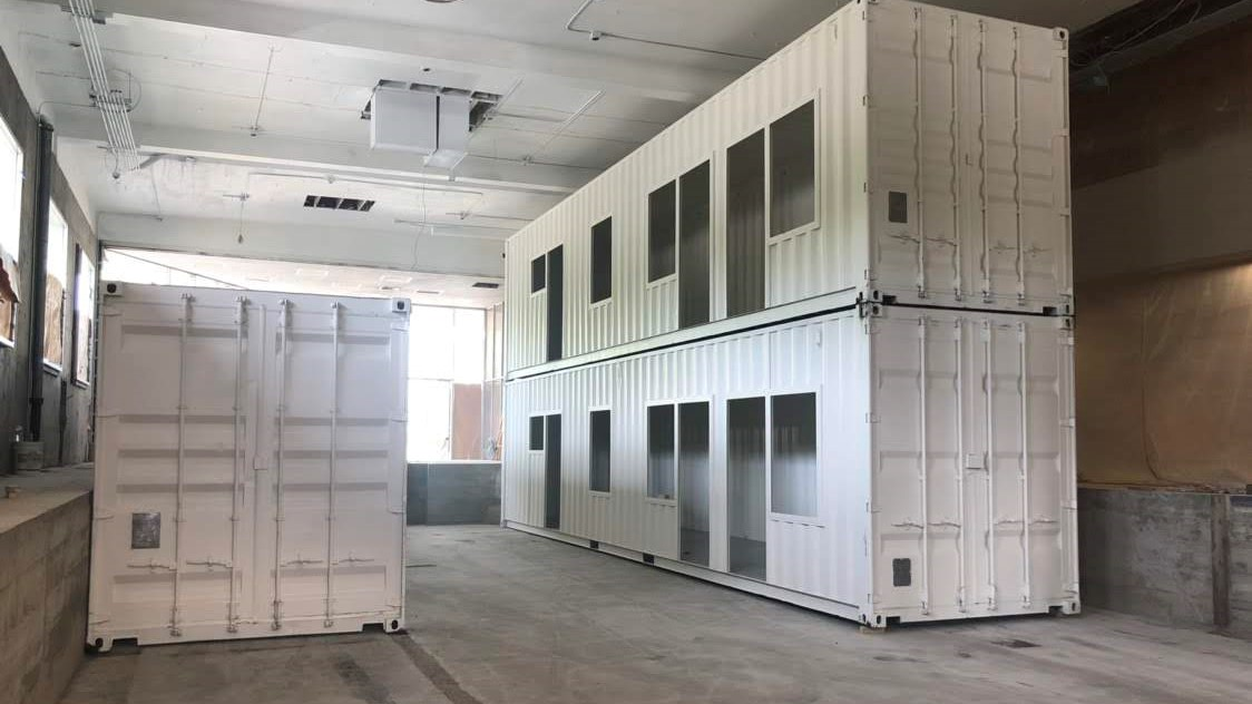 dual stacked shipping containers inside of warehouse